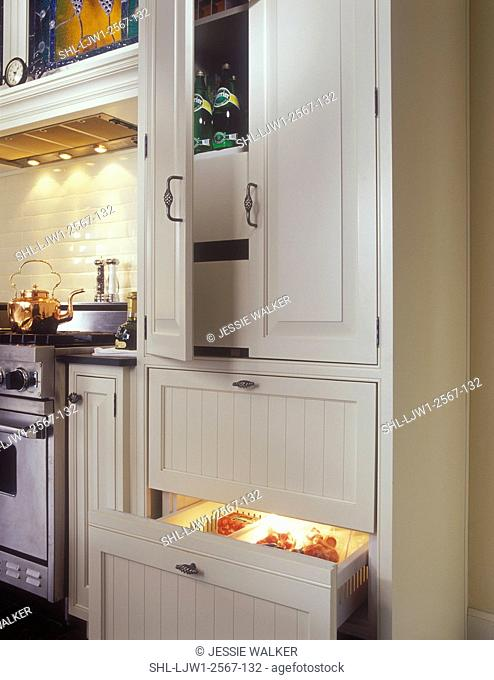 KITCHENS - Pantry on top of SUB-ZERO 700 series base freezer. Narrow pullouts on either side of range, white and stainless steel, raised panel cabinet doors