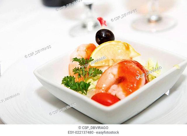 Shrimp Cocktail Garnished with Lemon Wedge and Black Olive