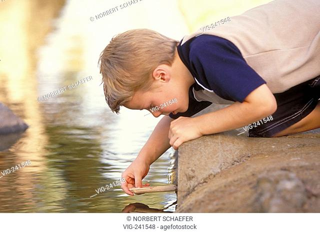 park-scene, portrait, full-figure, 10-year-old blond boy wearing blue-beige shirt and scater jeans kneels down at the coast playing with sticks  - GERMANY
