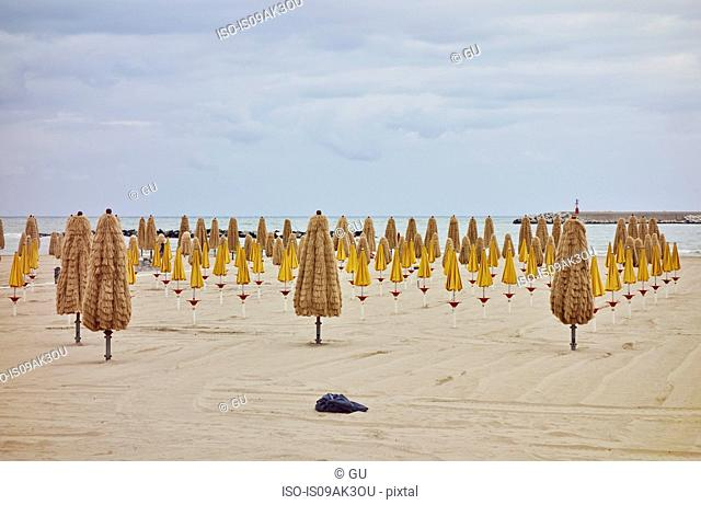 Rows of folded beach umbrellas on beach, Pescara, Abruzzo, Italy