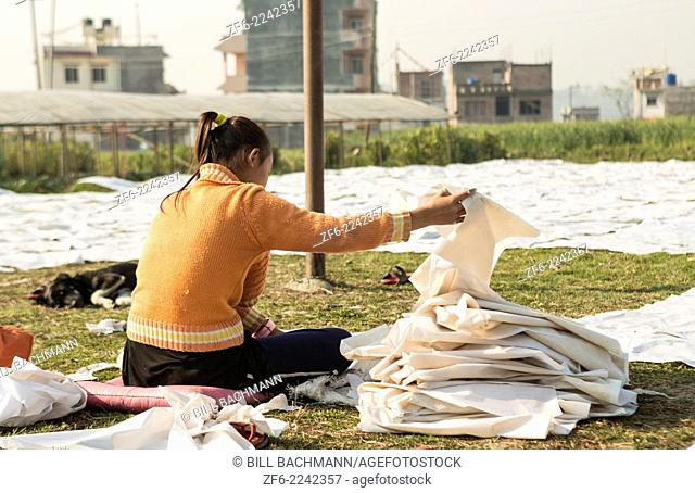 Kathmandu Nepal. working with newspaper spread on ground in Nayapati, Eastern Kathmandu. 34