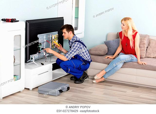 Young Woman Sitting On Couch Looking At Male Technician Repairing TV At Home