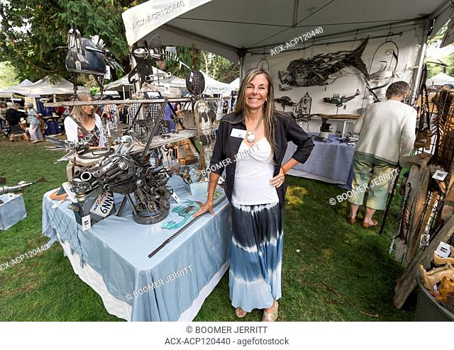An attractive artisan displays her welding creations at the Filberg Festival, Comox, The Comox Valley, Vancouver Island, British Columbia, Canada