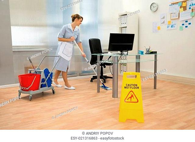 Young Maid Cleaning Floor With Mop In Office