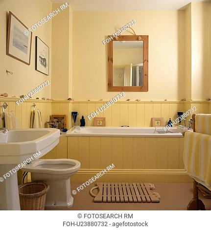 Wooden Mirror Above Dado Panelling And Panelled Bath In Pastel Yellow Bathroom With Bathmat