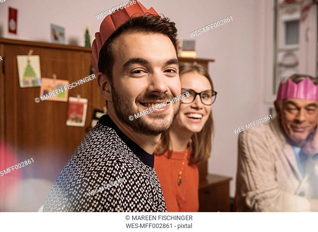 Smiling man wearing paper crown with family in background