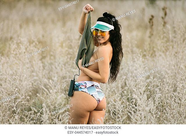 Young brunette woman undressed in the field with 80's style