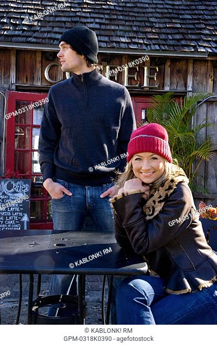 Portrait of young couple in warm clothing sitting at outdoor coffee shop