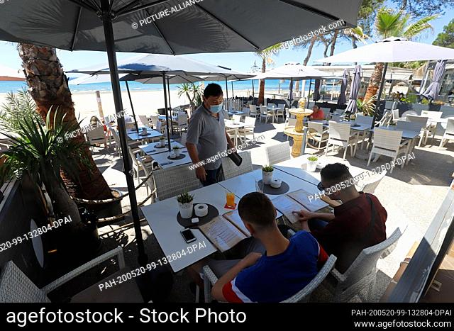 """20 May 2020, Spain, Calvia: A few Spanish friends order their food from a waiter on the terrace of the restaurant """"""""Momos"""""""" on the beach of Paguera"""