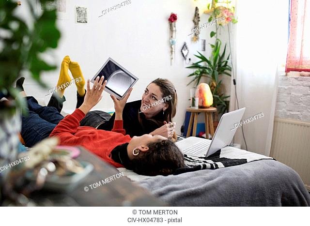 Young women friends relaxing, using digital tablet and laptop on bed