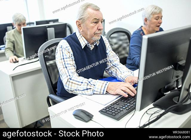 Active seniors attending computer course, working on PC