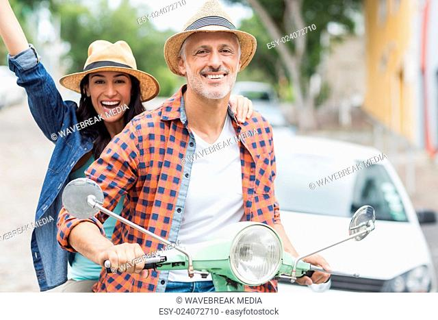 Portrait of man riding moped with excited woman