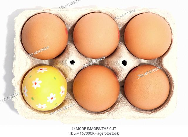 A box of eggs, one decorated