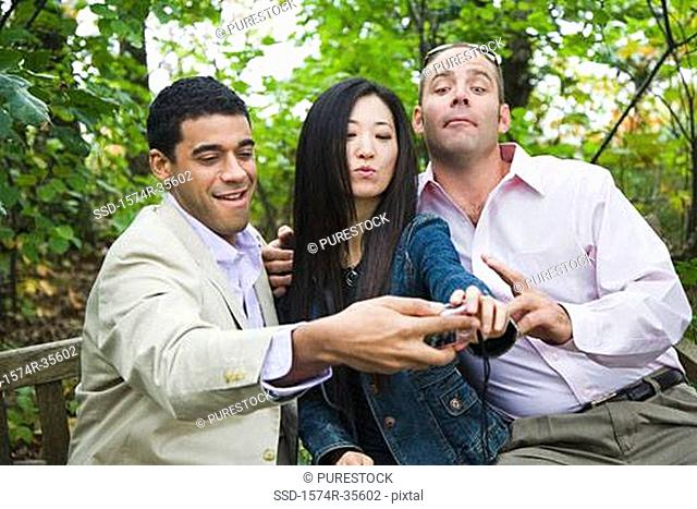 Friends taking picture of themselves with digital camera