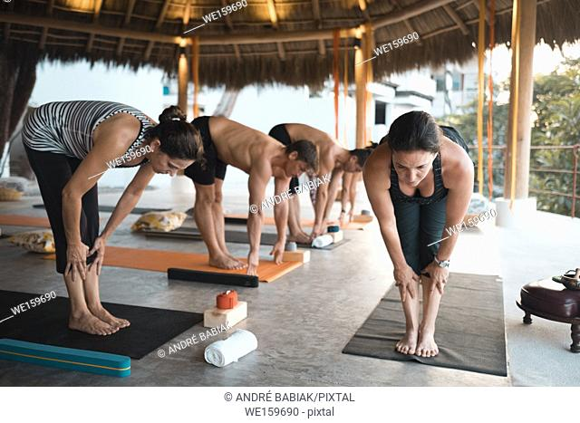 Group of motivated people exercising yoga at a retreat in Mexico