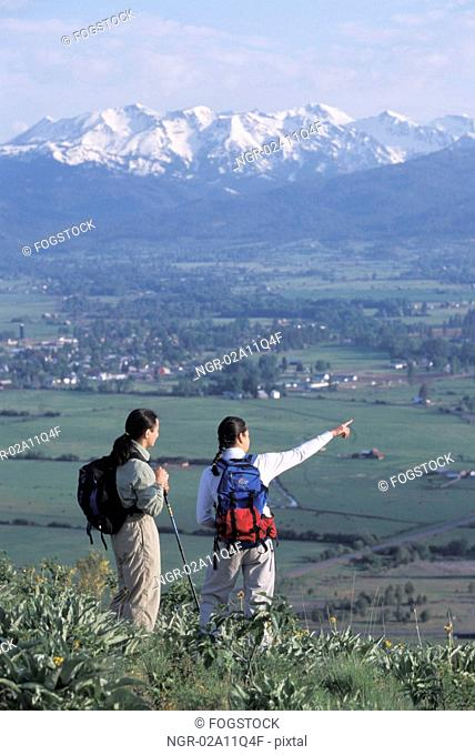 Hikers Standing On A Point Overlooking A Mountain Valley