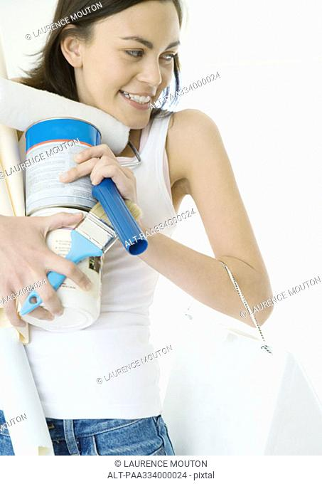 Woman holding armload of painting supplies