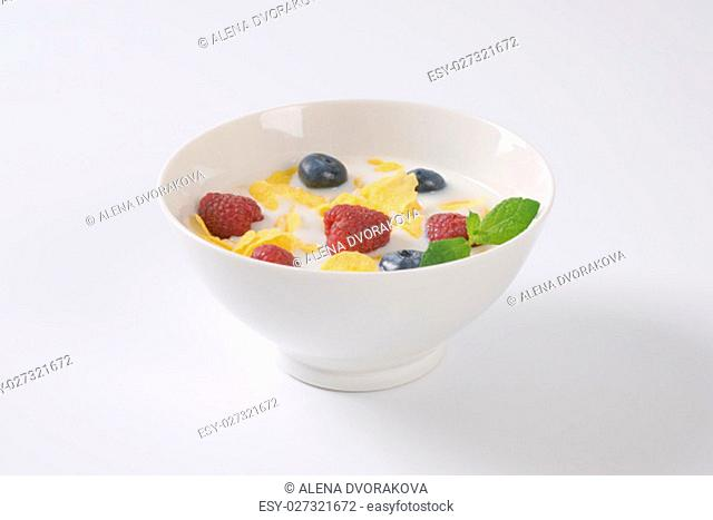 plate of corn flakes with milk and fresh berry fruit