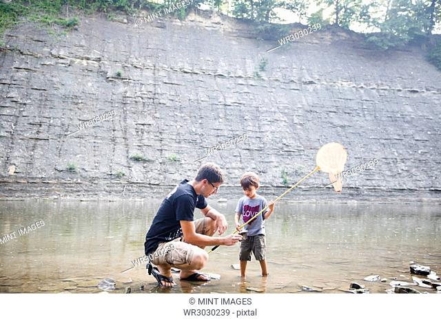 A father, man with a boy, child standing in the river holding a fishing net