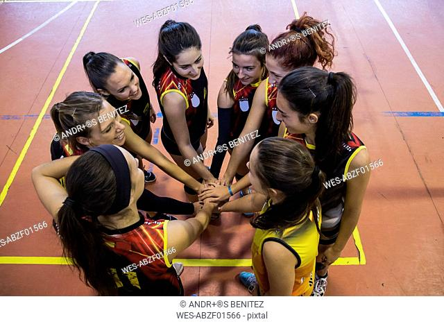 Female volleyball team huddling and stacking hands