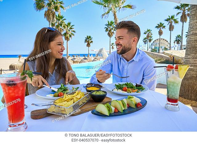 Young couple eating in a swimming pool restaurant