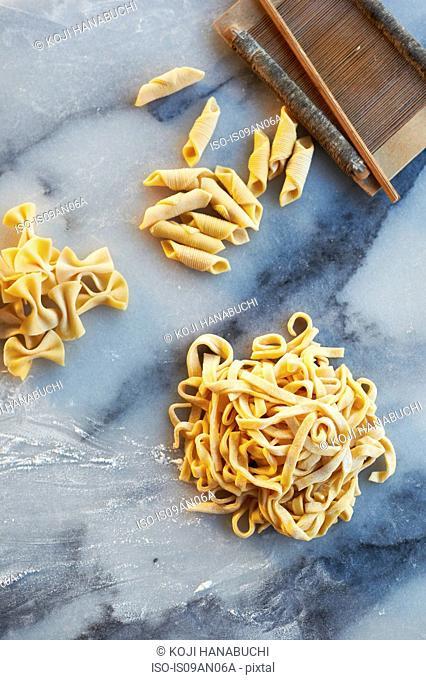 Freshly made pasta varieties on marble slab