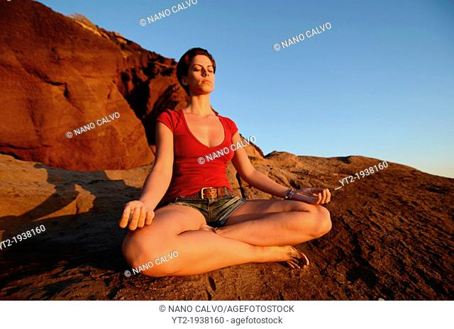 Young attractive woman meditates in lotus pose, in front of the coast