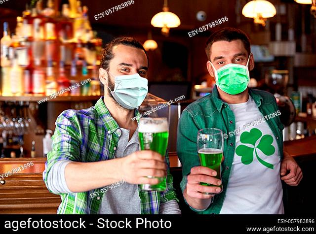 male friends in masks drinking green beer at bar