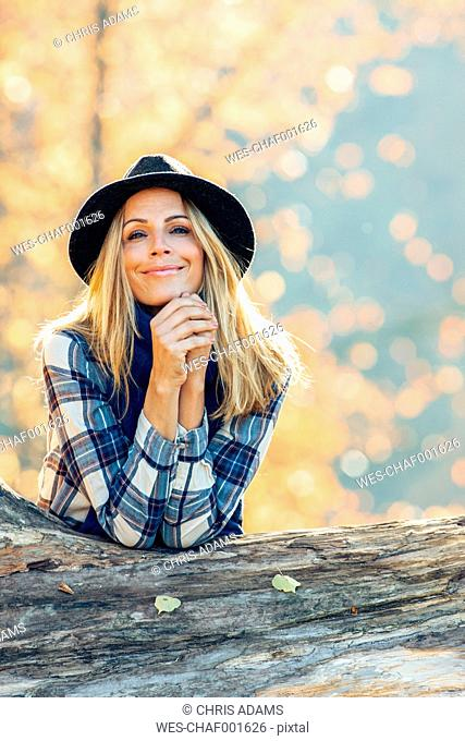 Smiling woman wearing a hat leaning on a trunk