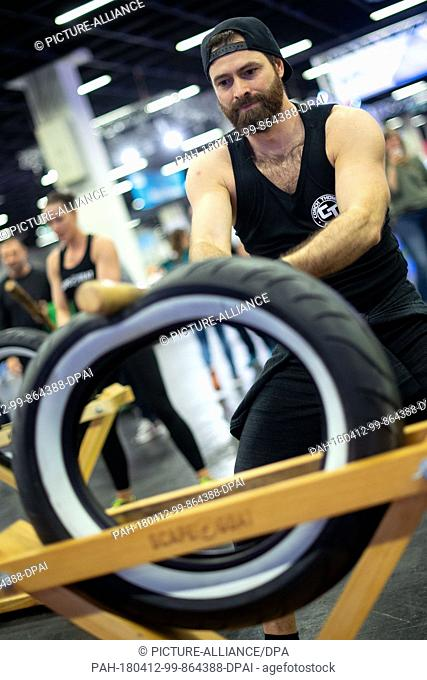 """12April 2018, Germany, Cologne: A model hits a tire with a bat during a demonstration of """"""""ScapeGoat"""""""". FIBO, the world's largest fitness trade show"""