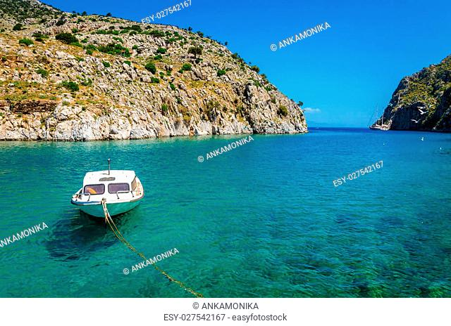 Small white motorboat anchored in sea bay with clear azure water, Greece