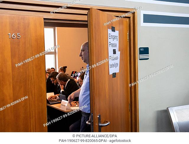 27 June 2019, North Rhine-Westphalia, Detmold: A member of the judicial staff closes the door of the hearing room. The arraignment shall take place in camera