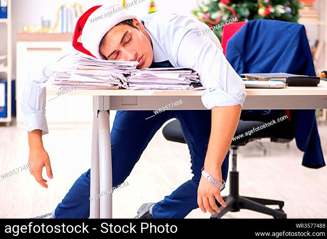 Young handsome employee celebrating Christmas at workplace