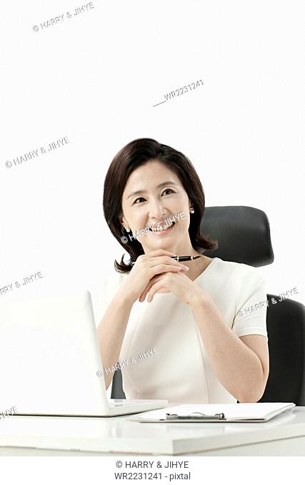 Middle aged business woman seated at desk with her laptop putting her hands under her chin and smiling