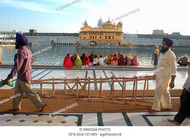 Sikh sitting on the marble steps of Amrit sarovar the lake of nectar ; Golden temple; Amritsar ; Punjab ; India