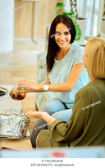 Pleasant interaction. Attractive joyful woman looking at her motherwhile pouring tea
