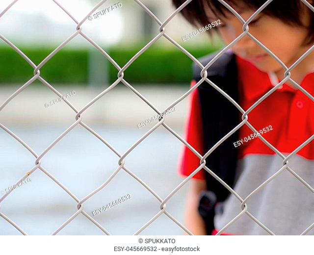 Portrait of handsome sad boy behind fence mesh netting. Emotions concept - sadness, sorrow, melancholy. Fashion & beauty concept