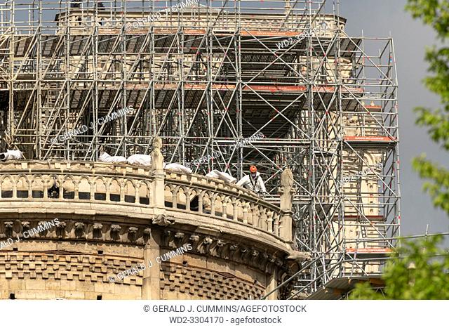 PARIS, FRANCE - 19 APRIL 2019 Notre Dame cathedral, a man removes charred timber from the roof. The remains of the melted scaffolding behind him is witness to...