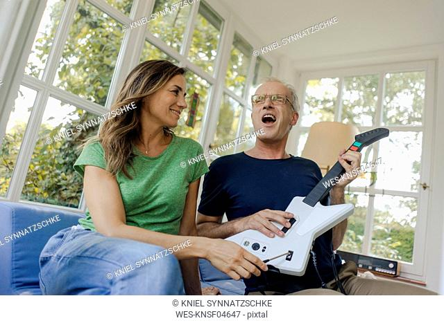 Happy mature couple sitting on couch at home with toy electric guitar