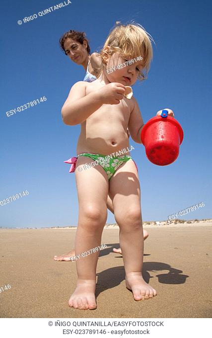 two years old blonde baby with pink and green swimsuit standing collecting and picking sea shells in red plastic bucket in hand with woman mother behind at...