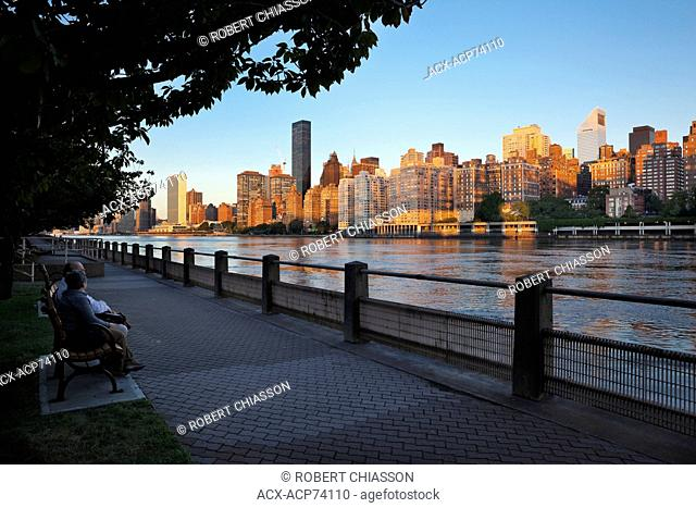 Lower East Side of midtown Manhattan at dawn as seen from Roosevelt Island. In the foreground is the East River, New York City, New York, U.S.A