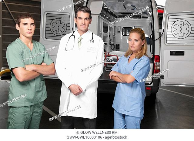 Doctor with co-workers standing in front of an ambulance