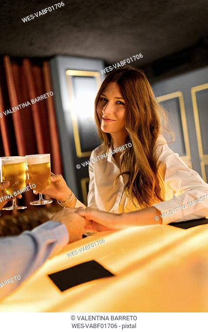 Portrait of smiling woman clinking beer glass with man in a bar