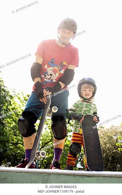 Father wit son holding skateboards