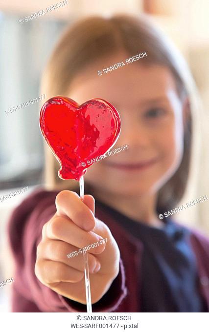 Girl holding heart-shaped lollipop