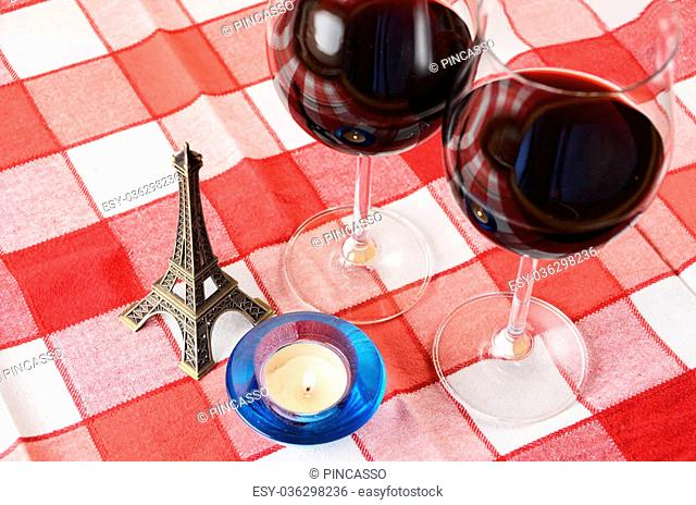 Souvenir Eiffel tower, candle and a pair of wineglasses on the table