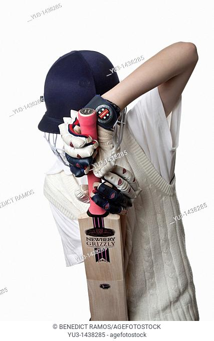 Young cricketer in protective helmet and gloves demonstrating a defensive shot