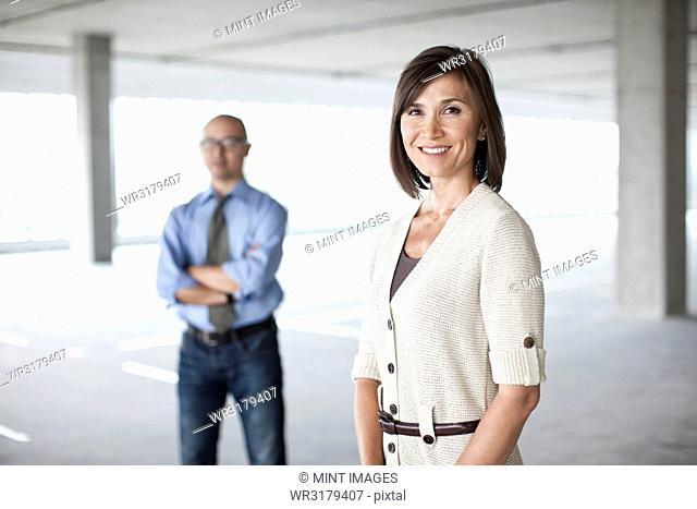 Caucasian businesswoman and Asian businessman standing in a large empty raw office space