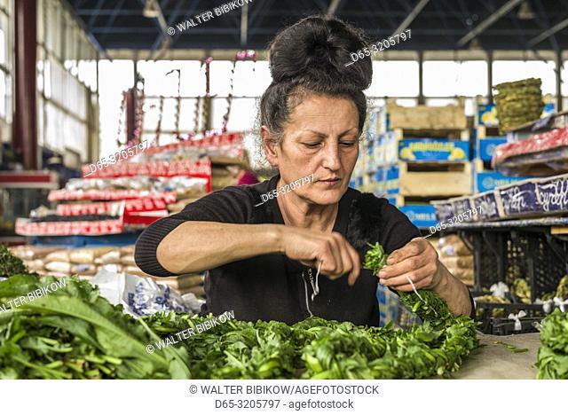 Armenia, Yerevan, G. U. M. Market, food market hall, woman braiding sorrel, MR