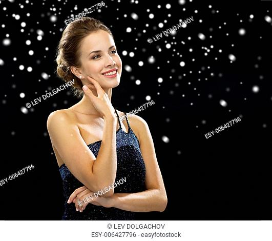 people, holidays and glamour concept - smiling woman in evening dress over black snowy background